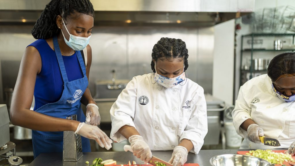 Quin Kelly (left) preparing meals for families of essential workers in the kitchen at Boys & Girls Club of America.