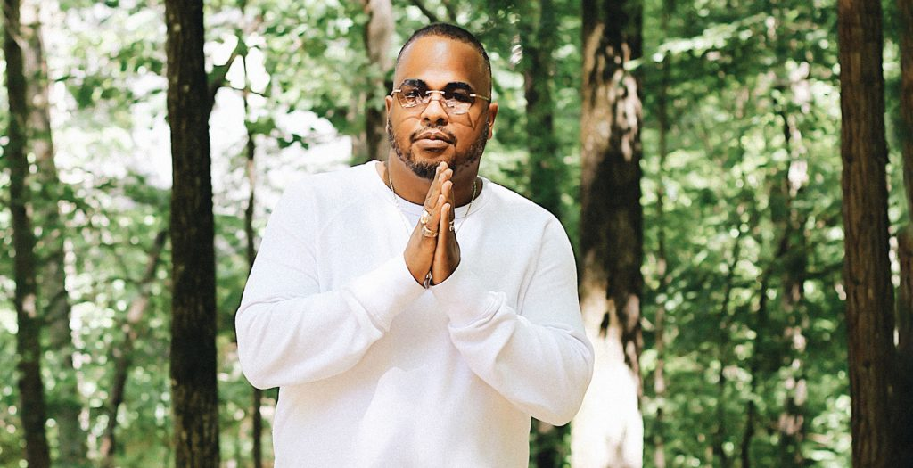 Producer Tricky Stewart strikes a yoga pose outdoors.